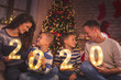canvas print picture Parents and kids holding illuminative numbers 2020