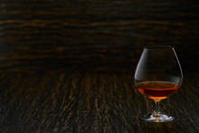 Full Glass Of Cognac On A Wood...