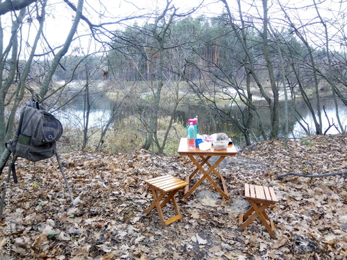 Montage in der Fensternische Camping Lunch by the river in a pine forest in autumn
