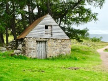 An Old Stone Barn In A Field