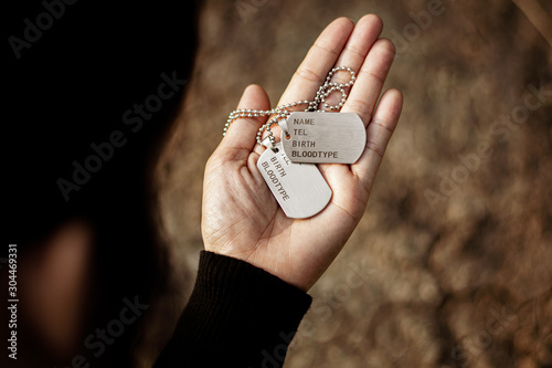 Photo  Blank military dog tags in women's hand