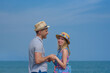 Young beautiful European couple standing on pier against amazing blue sea, they holding hands and enjoying their holidays.