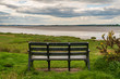 A bench at the Solway coast, looking at the Channel of River Esk in Bowness-on-Solway, Cumbria, England, UK