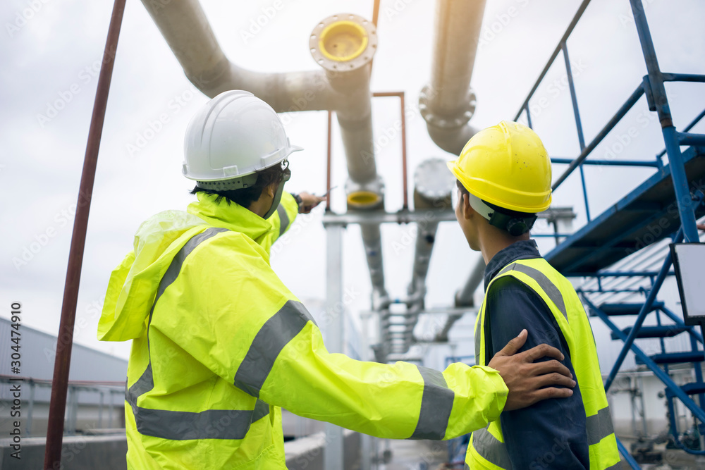 Fototapeta Mechanical engineer working install chilled water pipe system. Engineer consult discussion with team work for install pipe.