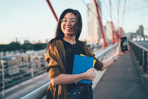 Fotomural  Half length portrait of happy female schooler with textbooks for education stand