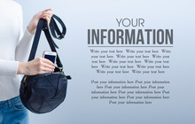 Woman Put Mobile Phone Into Black Bag On Gray Light Background, Space For Text