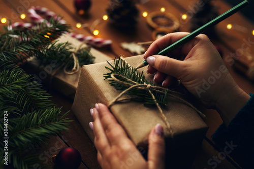 Fotobehang Vrouw gezicht Woman writes names on Christmas present