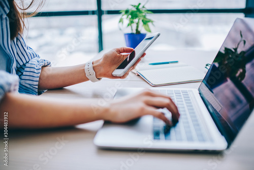 Fotografia Cropped image of female holding smartphone getting message with confirmation making transaction on laptop computer,woman using mobile phone app for synchronizing data with netbook via bluetooth