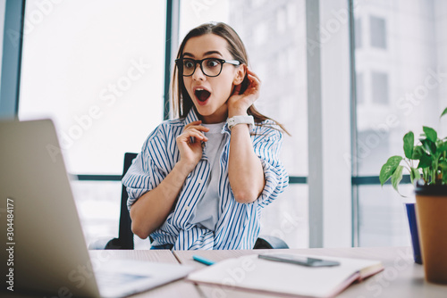 Emotional hipster girl surprised with getting victory in online contest reading news from laptop computer ,expressive young woman open mouth checking discounts for online shopping sitting at desktop Tablou Canvas