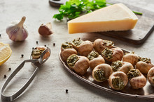 Selective Focus Of Delicious Cooked Escargots Near Lemon, Parmesan, Garlic, Parsley, Black Peppercorn And Tweezers On Stone Background