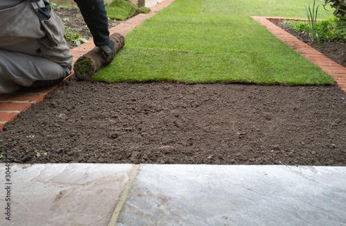 Fotografía New grass turf being installed in a garden along new brick edging