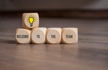 Cubes And Dice On Wooden Background With The Message Welcome To The Team