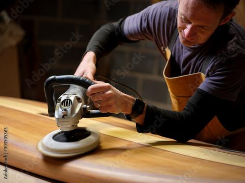 Man using sander on paddleboard - 304505363