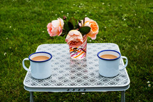 Two Enamel Mugs Of Tea And Flo...