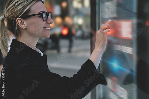Smiling female standing at big display with advanced digital technology Wallpaper Mural