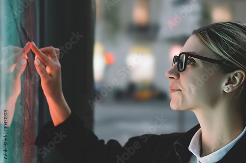 Photo Smiling female standing at big display with advanced digital technology