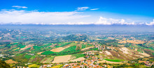 Aerial Top Panoramic View Of Landscape With Valley, Green Hills, Fields And Villages Of Republic San Marino Suburban District With Blue Sky White Clouds Background. View From San Marino Fortress.