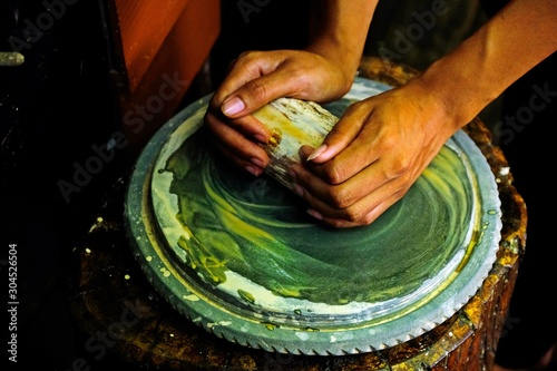 Photo  Woman hands grinding Thanaka (A yellowish-white cosmetic paste made from ground bark) on stone slab, The culture of Myanmar