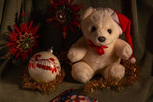 Christmas Composition - A White Teddy Bear In A Red Cap And With A Red Bank On His Neck Sits Next To A Christmas Ball And Other Christmas Decorations