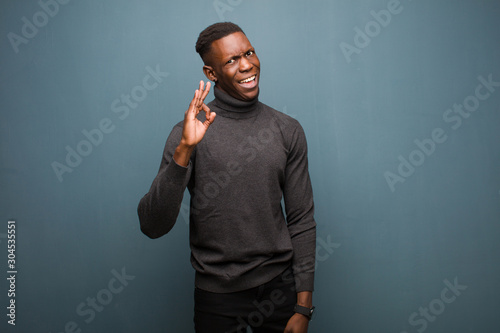 Photo young african american black man feeling successful and satisfied, smiling with