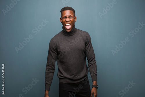 young african american black man feeling terrified and shocked, with mouth wide Fototapet