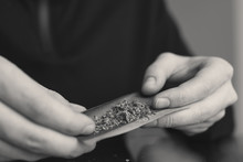Rolling A Marijuana Weed Joint . Close Up Weed Joint With Lighter. Smoke Pot Person. Man Rolling Cannabis Blunt.