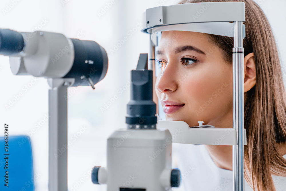 Fototapeta Beautiful young girl checking the eye vision in modern ophthalmology clinic