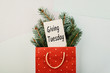 Leinwanddruck Bild - Giving Tuesday concept. Minimal flat lay with handwriting text Giving Tuesday in red gift bag and fir tree branches on pastel background.