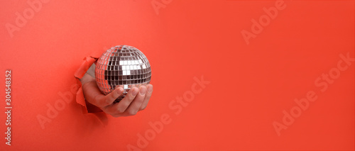 Hand holding Silver disco mirror ball on torn red paper wall. Copy space aside for your advertising and offer or sale content. - 304548352