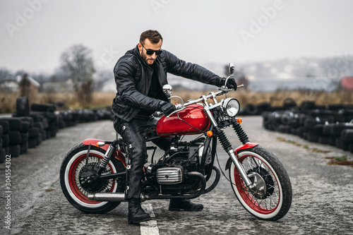 Red motorbike with rider. A man in a black leather jacket and pants stands sideways in the middle of the road. Tires are laid on the background - 304554302