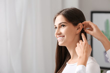 Woman Putting Hearing Aid In Young Girl's Ear At Home