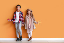 Fashionable Little Children In Autumn Clothes Near Color Wall