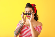 Portrait Of Beautiful Tattooed Pin-up Woman On Color Background