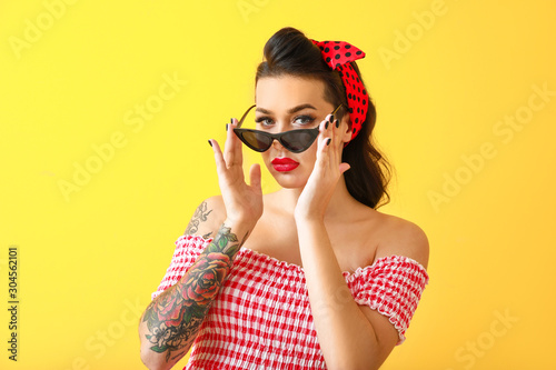 Fototapeta Portrait of beautiful tattooed pin-up woman on color background