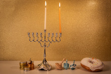Day 1 Of Jewish Religious Holiday Hanukkah With Traditional Chandelier Menorah, Spinning Top Toys (dreidels) And A Doughnut And Chocolate Coins On White Wooden Table And Golden Glittering Background