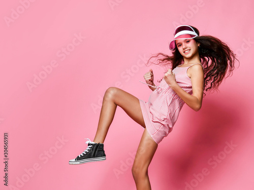 Fotomural  Beautiful teenager girl in a cap and pink striped dress joyfully shows a winner