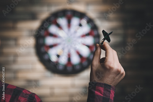 Photo Young man playing darts indoors