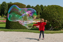 Girl Making Big Soap Bubbles In Park