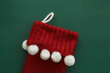 Red Knitted Christmas Stocking With White Pom Poms On Green Background, Copy Space