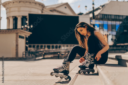 Stampa su Tela Young woman putting on skates going rollerblading in urban city