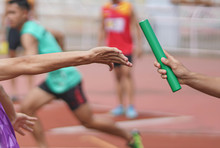 Professional Athlete Passing A Baton To The Partner Against Race On Racetrack.selective Focus.