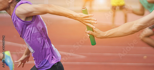Professional Athlete passing a baton to the partner against race on racetrack Fototapet