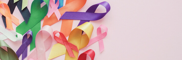 colorful ribbons on pink panoramic banner background, cancer awareness, World cancer day