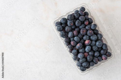 Vászonkép Open clamshell container of blueberries on a white granite counter
