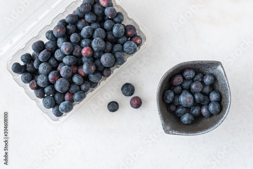 Valokuva Open clamshell container of blueberries on a white granite counter, small black