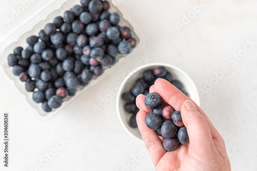 Woman's hand picking blueberries from clamshell container on a white granite cou Fototapet