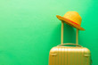 Leinwandbild Motiv Summer holidays, vacation and travel concept. Suitcase or luggage bag with sun hat on green background for copy space.