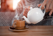 A Man Pours Tea From A Teapot In A CafeA Man Pours Tea From A Teapot In A Cafe