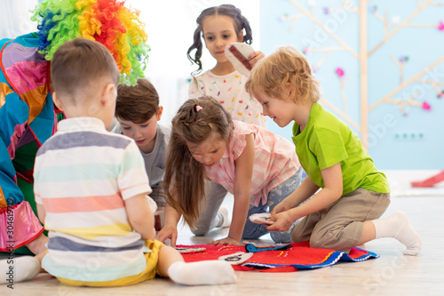 clown entertains preschool kids group on party