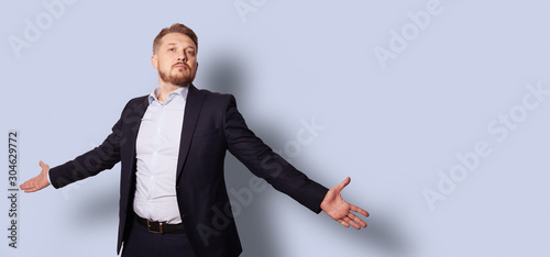 Handsome bearded man with open arms in a suit without a tie Canvas Print